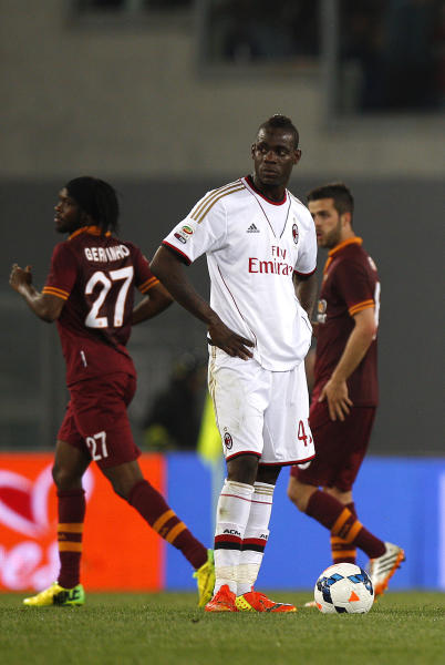 AC Milan's Mario Balotelli, center, stands by the ball after AS Roma midfielder Miralem Pjanic, right, scored during an Italian Serie A soccer match between Roma and AC Milan at Rome's Olympic stadium, Friday, April 25, 2014. (AP Photo/Alessandra Tarantino)