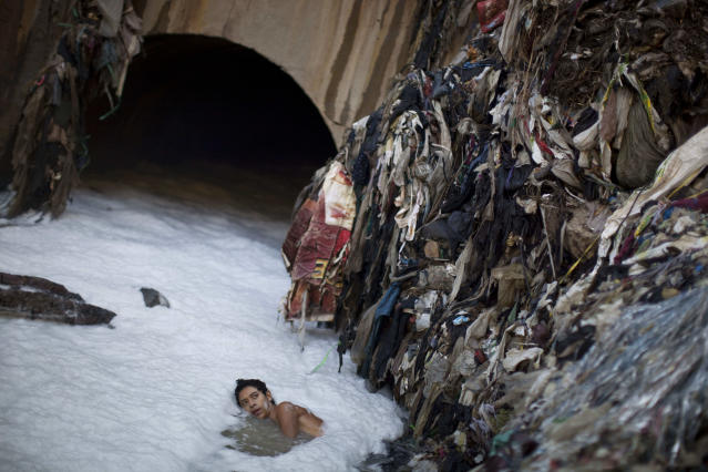 "<p>In this photo taken on Wednesday Oct. 19, 2011, a youth who goes by the name Paleta searches for metal in contaminated water by a tunnel where the water from sewage converges with storm water runoff at the bottom of one of the biggest trash dumps in the city, known as ""the Mine,"" in Guatemala City. (Photo: Rodrigo Abd/AP) </p>"