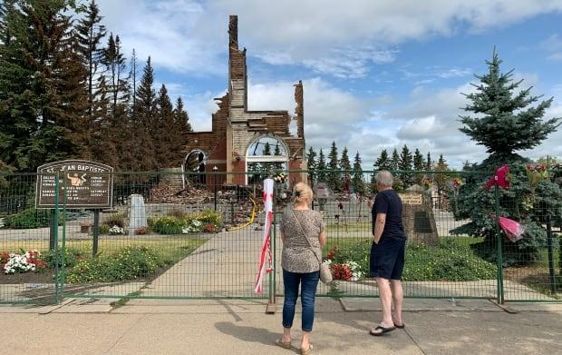 A steady stream of parishoners and Morinville residents visited the burned remains of outside the fence surrounding St. Jean Baptiste Catholic Church. (Andreane Williams/Radio-Canada - image credit)