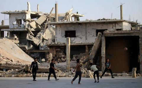 <span>Children play football in front of a damaged building in a rebel-held neighbourhood of Deraa in southern Syria</span> <span>Credit: AFP </span>