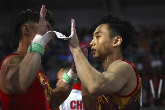 Zou Jingyuan of China, right, is congratulated by his teammates after his performance on the performs on the parellel bars in the men's team final at the Gymnastics World Championships in Stuttgart, Germany, Wednesday, Oct. 9, 2019. (AP Photo/Matthias Schrader)