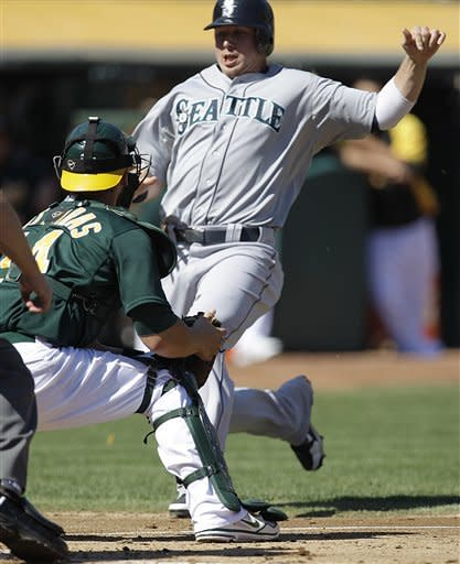 Oakland Athletics catcher George Kottaras, left, waits to tag out Seattle Mariners' Justin Smoak at home plate in the second inning of a baseball game Sunday, Sept. 30, 2012, in Oakland, Calif. Smoak attempted to score on a single by Carlos Triunfel. (AP Photo/Ben Margot)