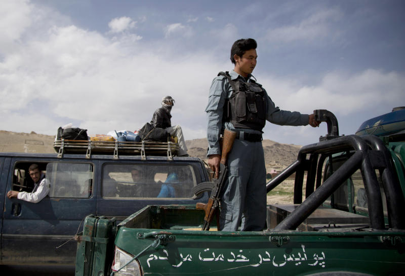 A police officer stands guard at a checkpoint on a road leading to Narkh district on the outskirts of Maidan Shahr in the Wardak province of Afghanistan on Wednesday, May 15, 2013. After reports of the disappearances of nine men from the area surfaced, President Hamid Karzai ordered all U.S. special operations forces to leave the entire province. An Afghan who once translated for the U.S. Special Forces was arrested on allegations of widespread torture and murder in connection with the disappearance and deaths of at least nine Afghans, the Afghan intelligence confirmed Monday, July 8, 2013. (AP Photo/Anja Niedringhaus)