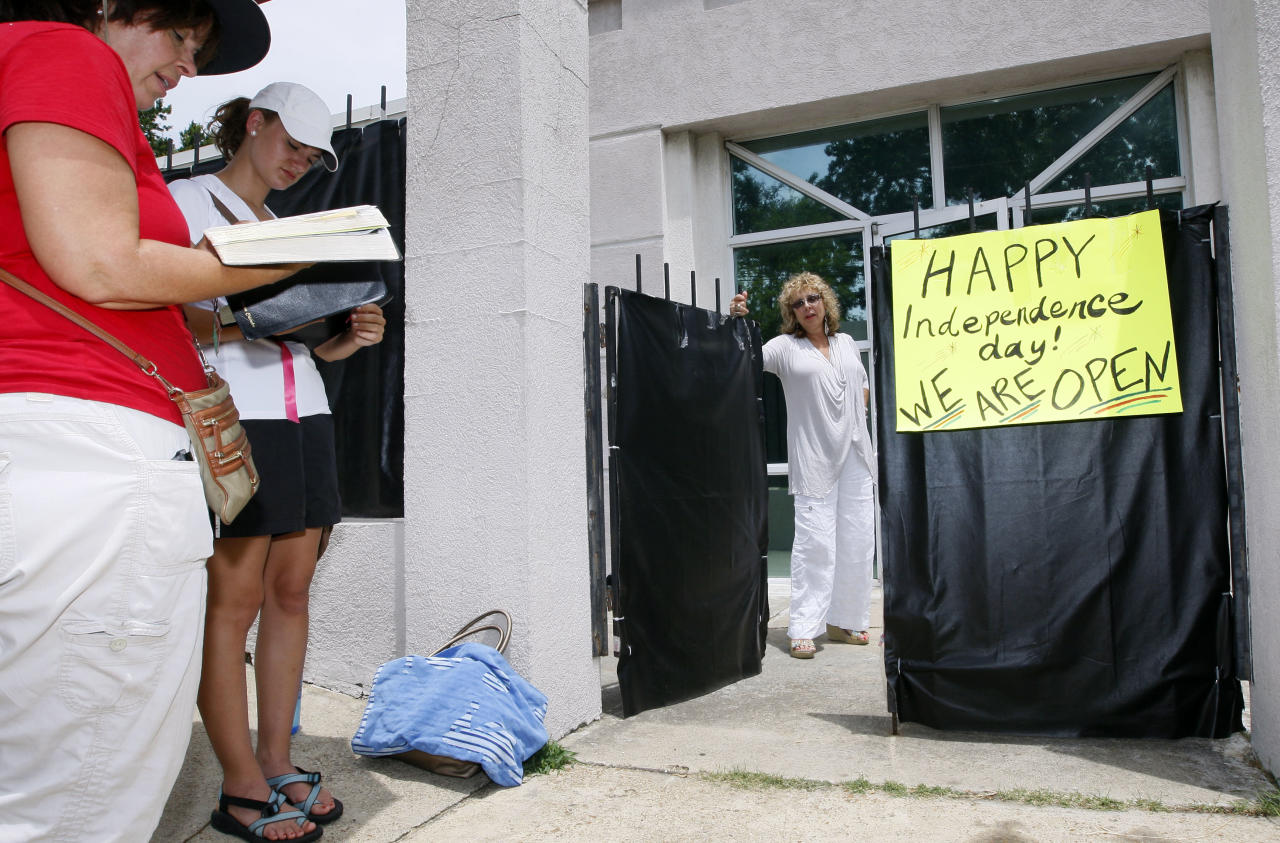 While abortion opponents pray, left, Jackson Women's Health Organization owner Diane Derzis poses at the gate of Mississippi's only abortion clinic in Jackson, Miss., Monday, July 2, 2012, after a federal judge issued a temporary restraining order Sunday, that blocked enforcement of a law that could regulate it out of business. The law would require any physician doing abortions at the clinic to be an OB-GYN with privileges to admit patients to a local hospital. (AP Photo/Rogelio V. Solis)