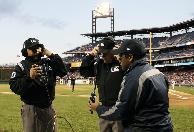 Second base umpire Adrian Johnson, left, and third base umpire Larry Vanover, center, listen to an instant replay call during the first inning of a baseball game between the Philadelphia Phillies and the Milwaukee Brewers, Wednesday, April 9, 2014, in Philadelphia. (AP Photo/Michael Perez)