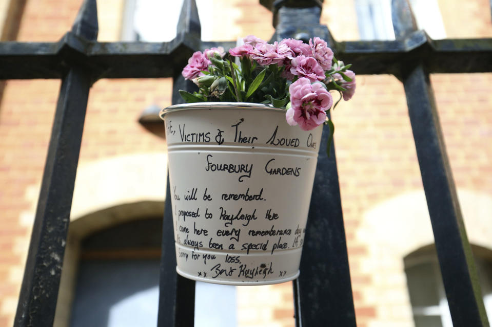 A floral tribute and message left at the Abbey gateway of Forbury Gardens following a multiple stabbing attack in the gardens, in Reading, England, Sunday June 21, 2020. British police are seeking the motive of a 25-year-old man suspected of stabbing three people to death in a daylight attack in a park. Detectives say they are not currently treating Saturday's attack in the town of Reading as terrorism, though the counterterrorism unit is supporting the investigation. Several other people were injured, three of them seriously, in an attack that came out of the blue on a sunny summer evening. (Jonathan Brady/PA via AP)