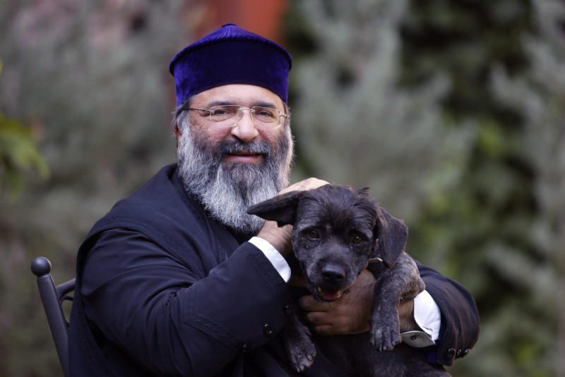 FILE - In this Oct. 21, 2005 file photo, Patriarch Mesrob II, the spiritual leader of Turkey's Armenian Orthodox community, holds his dog in Istanbul. Turkey's state-run Anadolu Agency said Mesrob Mutafyan, 62, the 84th Armenian Patriarch of Constantinople, died Friday, March 8, 2019 at Istanbul's Armenian Surp Pirgic hospital where he was being cared for. (AP Photo, File)