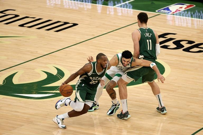 Milwaukee's Khris Middleton drives as teammate Brook Lopez sets a screen for Boston's Jayson Tatum in the Bucks' 121-119 NBA victory over the Celtics