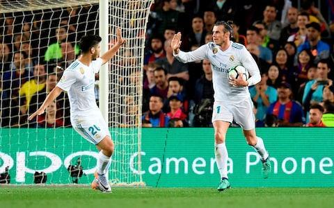 """Lionel Messi helped 10-man Barcelona remain undefeated in the Spanish league after drawing 2-2 with Real Madrid on Sunday in a testy El Clasico that saw Cristiano Ronaldo substituted at half-time with a leg injury. Ronaldo hurt his lower right leg while canceling out Luis Suarez's opener in the 10th minute. Gerard Pique stepped on his ankle as he unsuccessfully tried to stop the Madrid forward from scoring from close range. Ronaldo played on until half-time, when he was replaced by Marco Asensio. Madrid were dominating the match at Camp Nou and Barcelona right back Sergi Roberto was shown a direct red card in first-half injury time for swiping his hand at Marcelo's face as tempers flared between the rivals. But that was when Messi came to the hosts' rescue, sending the ball past Keylor Navas in the 52nd to swing the match back in Barcelona's favor despite playing a man down. Luis Suarez opens the scoring for Barcelona Credit: AP Gareth Bale pulled Madrid level again in the 72nd minute after curling in a pass by Asensio. Messi had more chances to grab the late winner but was denied by Navas. Barcelona remain unbeaten after 35 league matches this season and extended their record run to 42 Liga games without a loss. Their last league defeat came at Malaga in April 2017. Barcelona have matches left against Villarreal, Levante and Real Sociedad to try to become the first team to go unbeaten in the competition since the 1930s, when it consisted of merely 10 teams. Ronaldo, l'inquiétude https://t.co/sRHGHNM6eEpic.twitter.com/f4WLWR1fyD— L'actu du Sport (@LactuDuSport) May 6, 2018 Zinedine Zidane refused to put a time frame on Cristiano Ronaldo's injury absence. """"I don't know how long he'll be out,"""" the manager said. """"He said it wasn't much, but we'll see tomorrow. """"We'll do some tests to see the extent of the damage done to his ankle. He was a little worried because it was a bit swollen, but he said that it's nothing serious."""" 9:42PM FULL-TIME: BARCELONA 2-2 REAL MADRID An"""