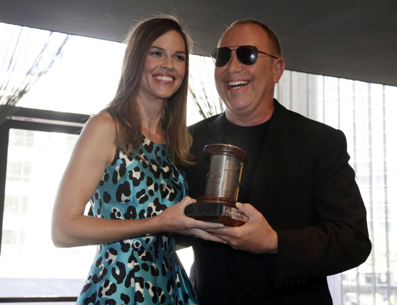 Designer Michael Kors receives 2013 The Couture Council Award for Artistry of Fashion from actress Hilary Swank during a luncheon in the David H. Koch Theater of New York's Lincoln Center, Wednesday, Sept. 4, 2013. The luncheon benefits the museum at the Fashion Institute of Technology in New York. (AP Photo/Richard Drew)