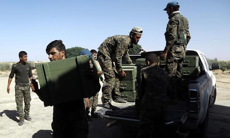 Syrian Democratic Forces (SDF) fighters unload boxes of ammunition supplied by the US-led coalition.