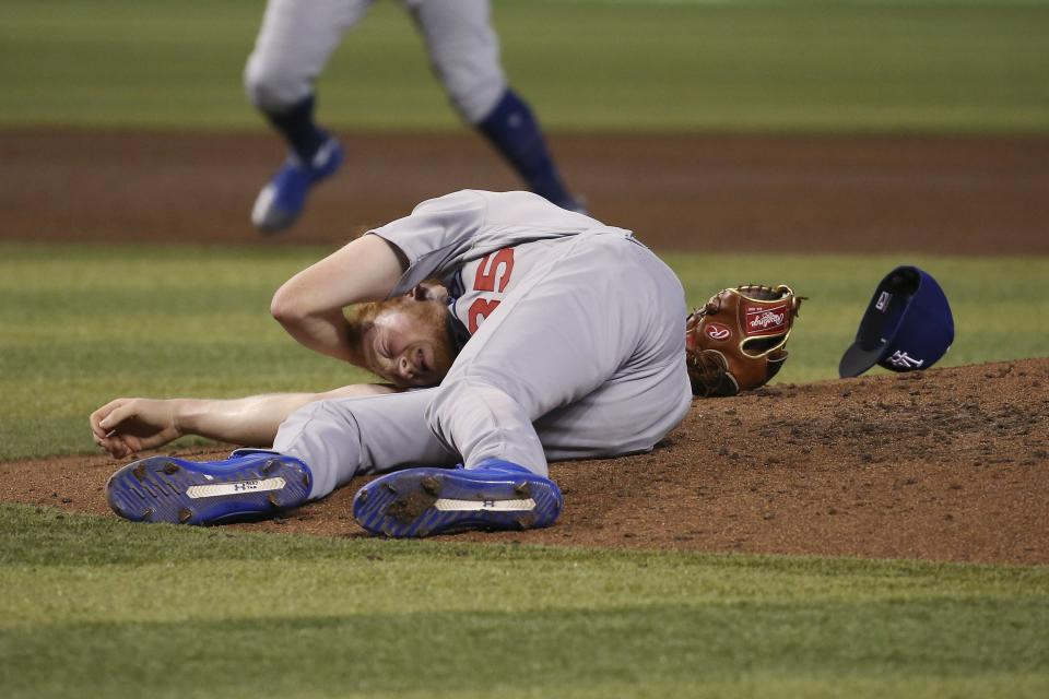 Los Angeles Dodgers relief pitcher Dustin May rolls on the ground after being hit by a batted ball from Arizona Diamondbacks' Jake Lamb during the fourth inning of a baseball game Sunday, Sept. 1, 2019, in Phoenix. (AP Photo/Ross D. Franklin)