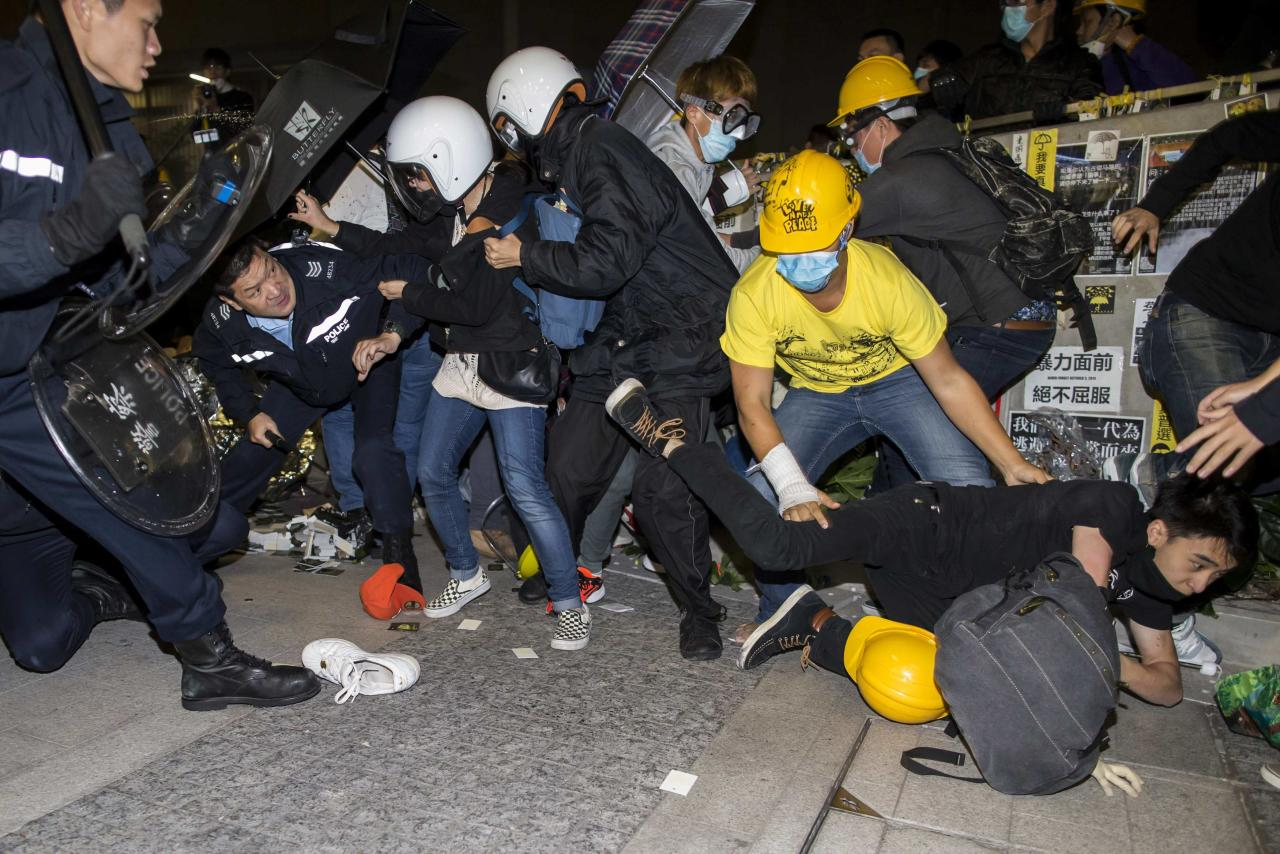 A protester falls on the ground as they are chased by riot police outside the Legislative Council in Hong Kong early November 19, 2014. A small group of Hong Kong pro-democracy protesters broke into the city's legislature via a side door early on Wednesday, and police stopped others storming the building as tensions jumped following a period of calm. REUTERS/Tyrone Siu (CHINA - Tags: POLITICS CIVIL UNREST EDUCATION)
