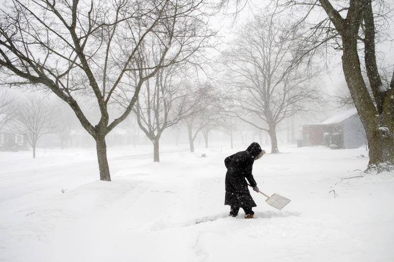 Abby Morin shovels a path as snow continues to fall on Friday, Feb. 8, 2019, in Grand Rapids, Mich. Morin said power was restored to her home the night before. (Neil Blake/The Grand Rapids Press via AP)