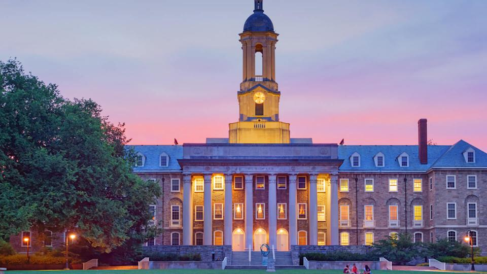 Students chat in front of Old Main, the main administrative building of Penn State after sunset.
