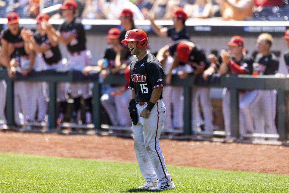 North Carolina State's J.T. Jarrett (15) celebrates after scoring off an RBI double hit by teammate Jonny Butler (14) against Stanford in the fourth inning in the opening baseball game of the College World Series, Saturday, June 19, 2021, at TD Ameritrade Park in Omaha, Neb. (AP Photo/Rebecca S. Gratz)