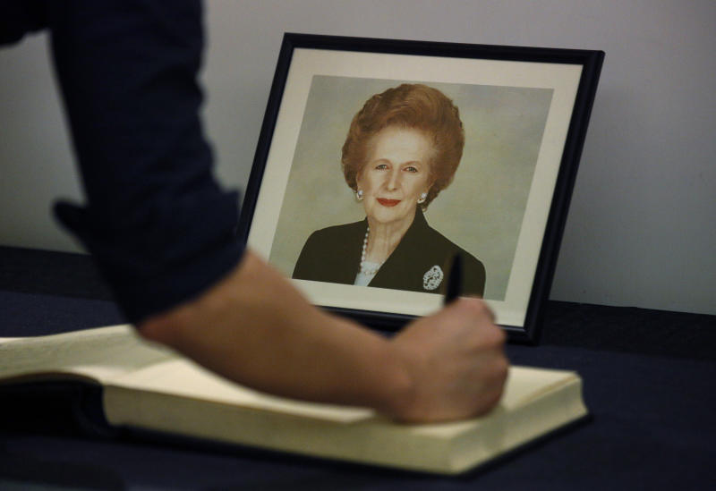 A man signs the condolence book in front of a  picture of former British Prime Minister Margaret Thatcher at the British Consulate in Hong Kong Tuesday, April. 9, 2013. Her spokesman said Thatcher died Monday morning of a stroke. (AP Photo/Vincent Yu)