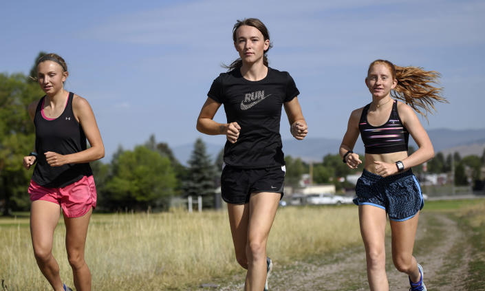 """FILE - In this Aug. 15, 2019, file photo, is University of Montana cross country runner Juniper Eastwood, center, warming up with her teammates at Campbell Park in Missoula, Mont. Transgender kids would be banned from playing on school sports teams for the gender with which they identify under a GOP-backed bill that advanced Thursday, Jan. 21, 2021, in Montana. The proposed ban is personal for people like Eastwood, a transgender woman and former member of the University of Montana's track and field and cross-country running teams. She said the legislation """"would make it impossible for other young Montanans like me to participate in sports as who they are."""" (Rachel Leathe/Bozeman Daily Chronicle via AP, file)"""