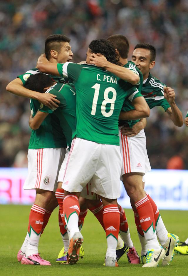 Mexico's Oribe Peralta, left, is congratulated by teammates after scoring against Panama during a 2014 World Cup qualifying match in Mexico City, Friday, Oct. 11, 2013. (AP Photo/Christian Palma)
