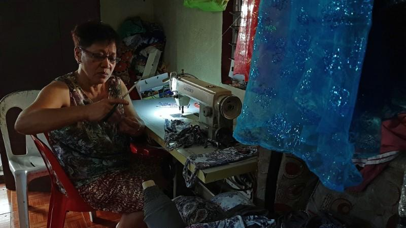 A seamstress sews protective masks to be donated to residents affected by the erupting Taal Volcano