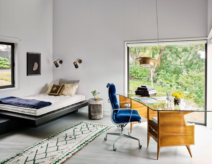 "<div class=""caption""> A glass-topped desk designed by Gio Ponti dominates a cantilevered office area off the kitchen; it sits opposite a custom bed platform highlighted by Yayoi Kusama artwork. </div>"
