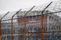 FILE - This March 16, 2011 file photo shows a barbed wire fence outside inmate housing on New York's Rikers Island correctional facility in New York. New York City's notorious Rikers Island jail complex, troubled by years of neglect, has spiraled into turmoil during the coronavirus pandemic. (AP Photo/Bebeto Matthews, File)