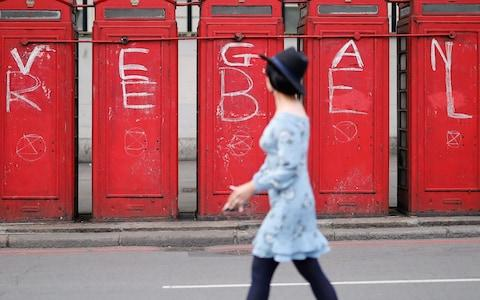 "A pedestrian walks past public telephone boxes daubed with the words ""vegan"" and ""rebel"" and the symbol of the Extinction Rebellion environmental protest group in London in April - Credit: AFP"