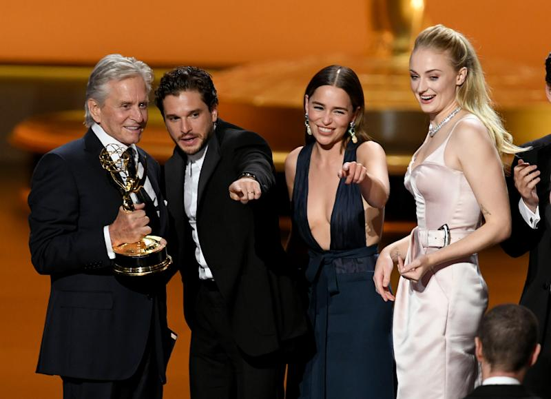 "Michael Douglas presents the Outstanding Drama Series award for ""Game of Thrones"" to Kit Harington, Emilia Clarke and Sophie Turner. (Photo: Getty Images)"