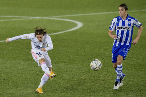 Real Madrid's Luka Modric, left, tries a shot during the Spanish La Liga soccer match between Alaves and Real Madrid at Mendizorroza stadium in Vitoria, Spain, Saturday, Jan. 23, 2021. (AP Photo/Alvaro Barrientos)