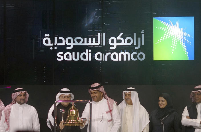 Saudi Arabia's state-owned oil company Armco and stock market officials celebrate during the official ceremony marking the debut of Aramco's initial public offering (IPO) on the Riyadh's stock market, in Riyadh, Saudi Arabia, Wednesday, Dec. 11, 2019. (AP Photo/Amr Nabil)