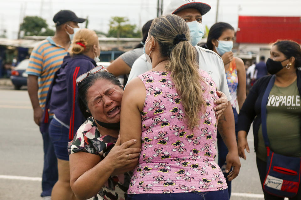 Relatives of inmates cry outside the Centro de Privación de Libertad Zona 8 prison where riots broke out in Guayaquil, Ecuador, Tuesday, Feb. 23, 2021. Deadly riots broke out in prisons in three cities across the country due to fights between rival gangs, according to police. (AP Photo/Angel Dejesus)