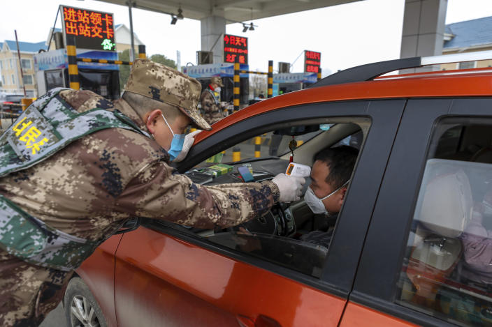 FILE - In this Jan. 23, 2020, file photo, a militia member uses a digital thermometer to take a driver's temperature at a checkpoint at a highway toll gate in Wuhan in central China's Hubei Province. The Chinese city of Wuhan is looking back on a year since it was placed under a 76-day lockdown beginning Jan. 23, 2020. (Chinatopix via AP, File)