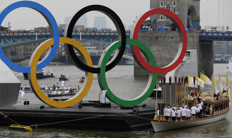 The royal barge Gloriana carries the Olympic flame along the river Thames,  ahead of the 2012 Summer Olympics, on the final day of the Torch Relay, Friday, July 27, 2012, in London. The opening ceremonies for the 2012 London Olympics will be held Friday evening. (AP Photo/Kirsty Wigglesworth)(AP Photo/Kirsty Wigglesworth)