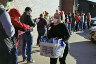 Connie Clark, with the Douglas County Election Commission, wears a costume for Halloween, as she distributes forms to those in line to vote early, in Omaha, Neb., Saturday, Oct. 31, 2020. (AP Photo/Nati Harnik)