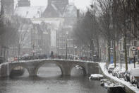 A man crosses a bridge in the near-empty Red Light District in Amsterdam, as snow and strong winds blanketed much of the Netherlands, Sunday, Feb. 7, 2021. (AP Photo/Peter Dejong)
