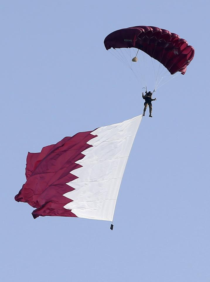 A paraglider, with the national flag, flies over the capital during National Day celebrations in Doha