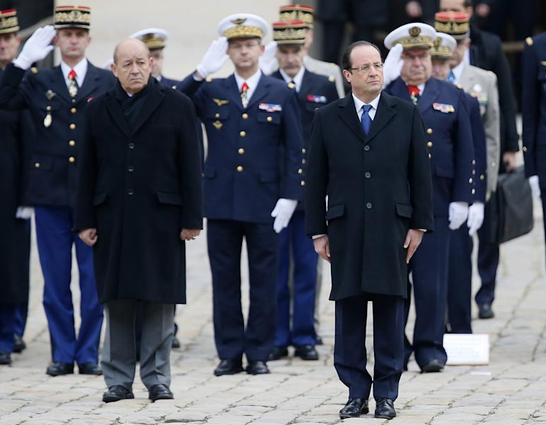 French President Francois Hollande, right, and Defense Minister Jean-Yves Le Drian reviews the troops during a military ceremony, Tuesday, Nov. 26, 2013, at the Invalides in Paris. France will send 1,000 troops to Central African Republic under an expected U.N.-backed mission to keep growing chaos at bay, the defense minister said Tuesday — boosting the French military presence in Africa for the second time this year. (AP Photo/Patrick Kovarik, Pool)