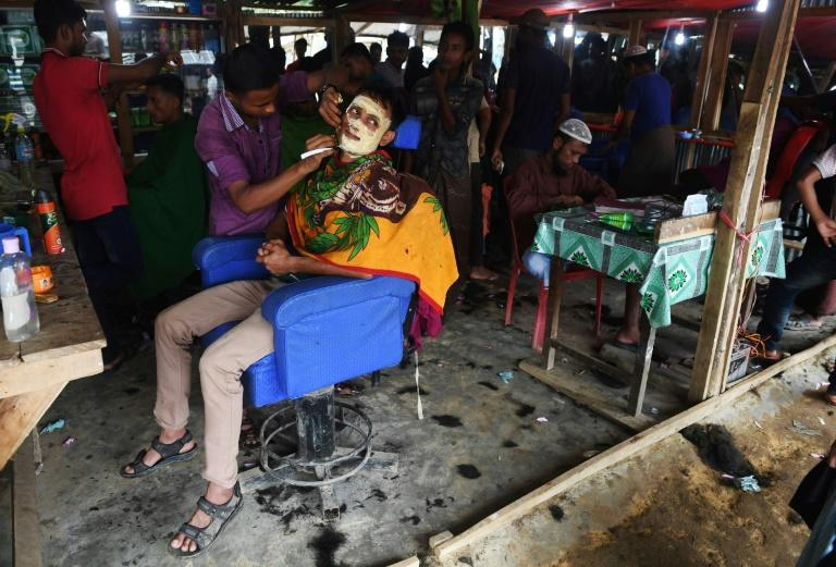 Rohingya refugees get treatments at a men's salon ahead of the Eid Al-Adha festival at the Balukhali refugee camp near Cox's Bazar