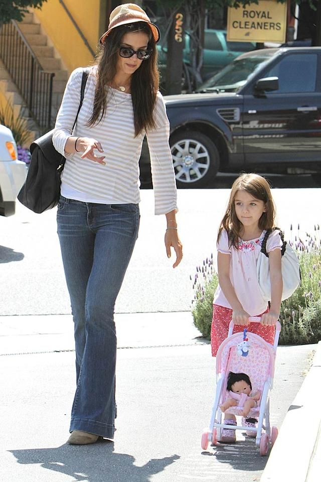 """Katie Holmes and 5-year-old Suri spent some of their Saturday perusing L.A.'s Brentwood Country Mart, filled with swanky shops and eateries. Looks like little Suri can't wait to grow up and become a mom herself someday! <a href=""""http://www.infdaily.com"""" target=""""new"""">INFDaily.com</a> - August 6, 2011"""