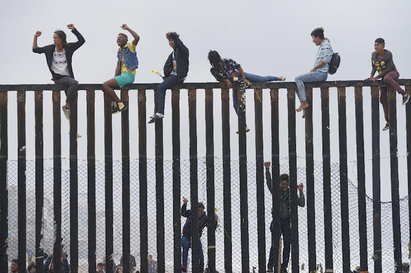 Pro-migrant caravan demonstrators climb the US-Mexico border fence during a rally, on April 29, 2018, in San Ysidro, California (AFP Photo/Sandy Huffaker)