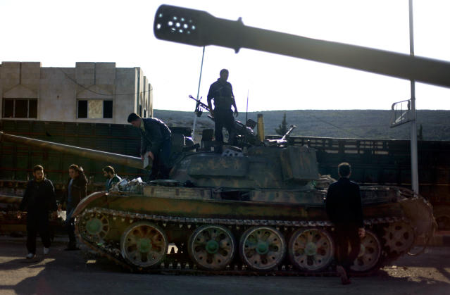 In this Monday, Nov. 19, 2012 file photo, Syrian fighters stand on a tank they took after storming a military base in Aleppo. Through mid-2012, rebel power grew and Assad's army ramped up its response. Relentless government shelling leveled neighborhoods and killed hundreds. Regular reports emerged of mass killings by the regime or thugs loyal to it, pushing more Syrians toward armed struggle. The government, which considers the opposition terrorist gangs backed by foreign powers, denied any role, and does not respond to requests for comment on its military. The rebels, too, were accused of atrocities. (AP Photo/ Khalil Hamra)