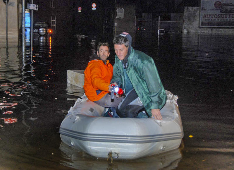 Two men use an inflatable dingy to get around in a flooded street in Olbia, northern Sardinia, Monday, Nov. 18, 2013. A violent rainstorm that flooded entire parts of the Mediterranean island of Sardinia has led to the deaths of at least nine people. Bridges were felled by swollen rivers and water levels reached 3 metres (yards) in some places. (AP Photo/Antonio Satta)