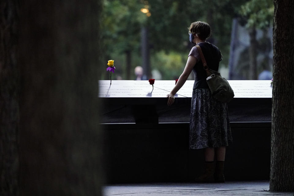A mourner stands at the south pool before ceremonies to commemorate the 20th anniversary of the Sept. 11 terrorist attacks, Saturday, Sept. 11, 2021, at the National September 11 Memorial & Museum in New York. (AP Photo/John Minchillo)
