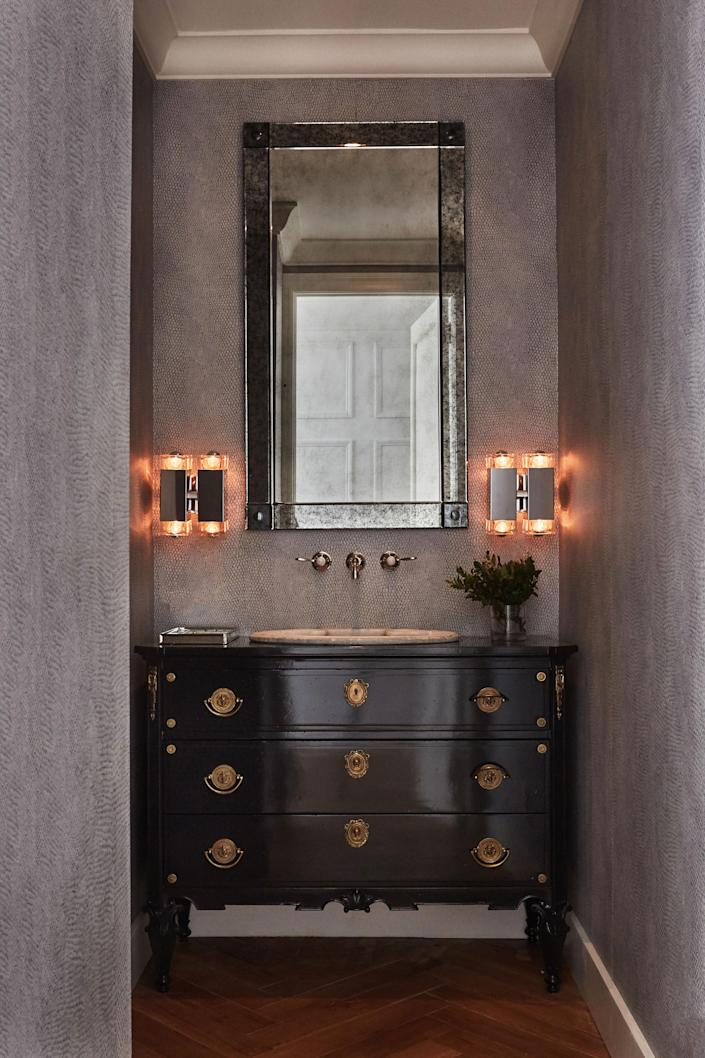 The vintage sink—a marble piece from the 1930s—is one of the only objects Blinken kept from the original apartment. The vanity is a refurbished chest from an antiques store. Inspired by a friend's snakeskin clutch, Blinken sourced the custom lizard print wallpaper to add a textural note to the powder room. The lights are from Olde Good Things.