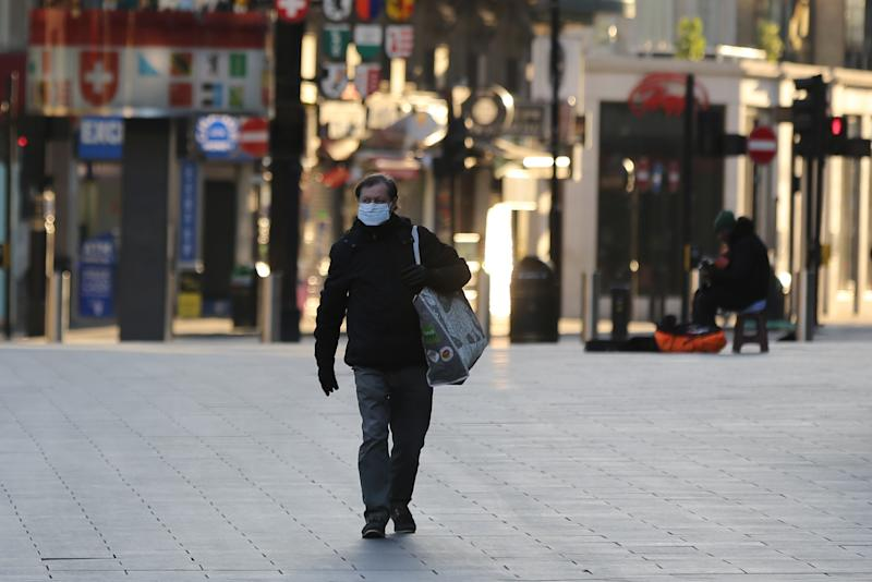 LONDON, UNITED KINGDOM - MARCH 23: A man wears a medical mask as a precaution against coronavirus (Covid-19) at deserted Leicester Square in London, United Kingdom on March 23, 2020. Total number of deaths due to coronavirus reached 335 today in UK. (Photo by Ilyas Tayfun Salci/Anadolu Agency via Getty Images)
