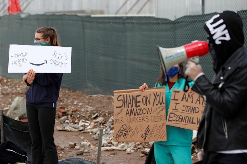 Demonstrators hold signs as they listen to former Amazon employee, Christian Smalls, speak during a protest outside of an Amazon warehouse as the outbreak of the coronavirus disease (COVID-19) continues in the Staten Island borough of New York U.S., May 1, 2020. REUTERS/Lucas Jackson
