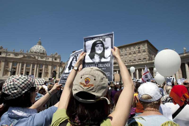 "FILE - In this Sunday, May 27, 2012 file photo, people hold pictures of Emanuela Orlandi reading, ""march for truth and justice for Emanuela"" in St. Peter's square, at the Vatican. An expert for the family of a Vatican teenager who went missing in 1983 says there are thousands of bones in an underground space near a Vatican cemetery. Giorgio Portera, engaged by Emanuela Orlandi's family, said the extent of the cache emerged Saturday when Vatican-appointed experts began cataloguing the remains discovered on July 13. Portera said skulls and bones appear to belong to dozens of individuals. The Vatican made no mention of the number but said analyses would resume on July 27. (AP Photo/Andrew Medichini, File)"