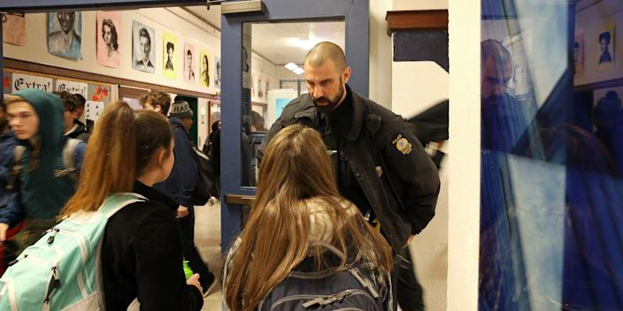 A Portland police officer talks to students in the Portland High School hallway in November 2019.