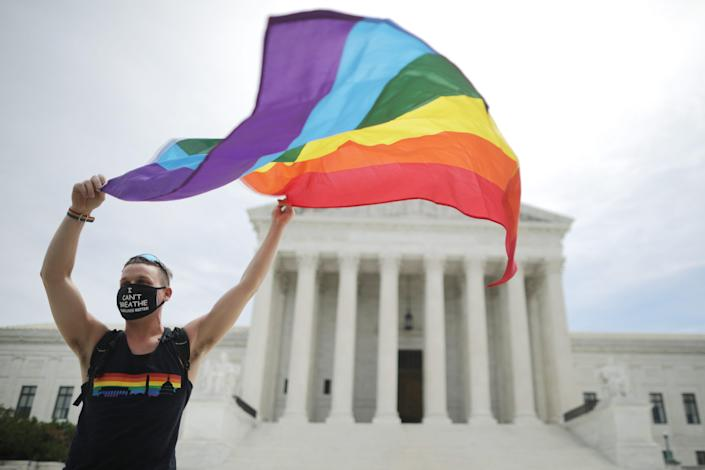 Joseph Fons holds a Pride Flag in front of the U.S. Supreme Court building after the court ruled that LGBTQ people can not be disciplined or fired based on their sexual orientation June 15, 2020 in Washington, DC.