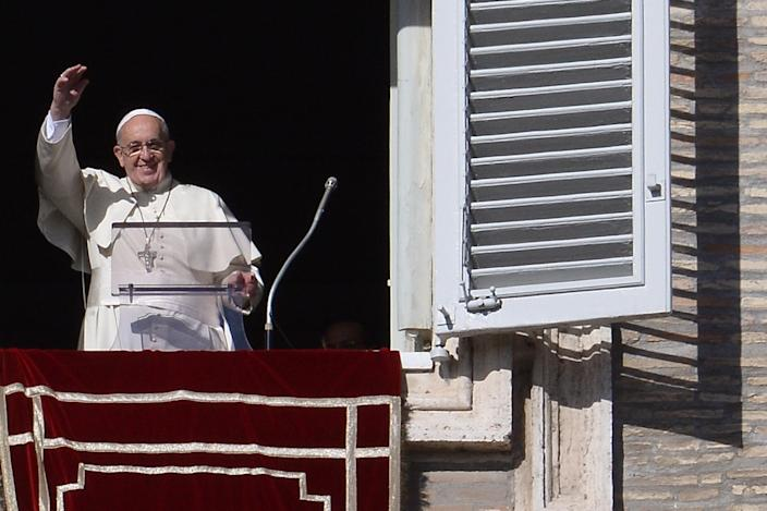 Pope Francis salutes the crowd from the window of the apostolic palace overlooking St.Peter's Square at the Vatican, on November 16, 2014 (AFP Photo/Filippo Monteforte)